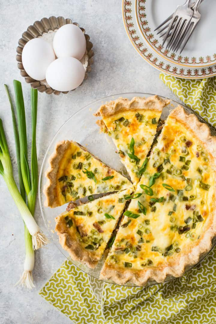 Overhead image of quiche Lorraine with eggs and fresh scallions.