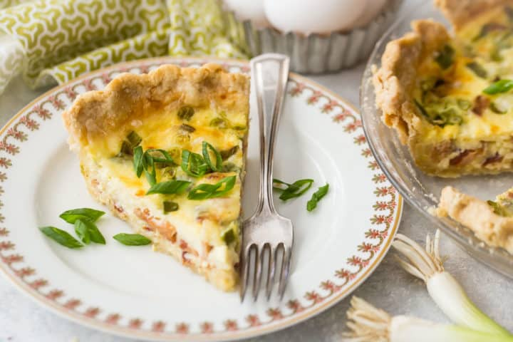 Slice of quiche Lorraine on a china plate with a silver fork and fresh sliced scallions.