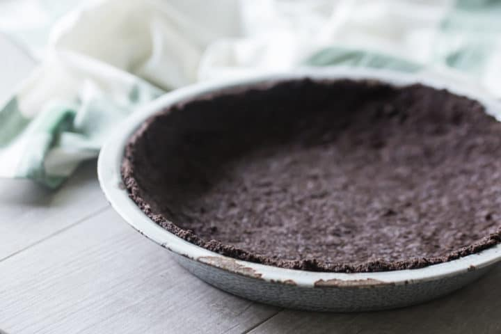 Homemade oreo cookie crust in a vintage enamel pie dish.