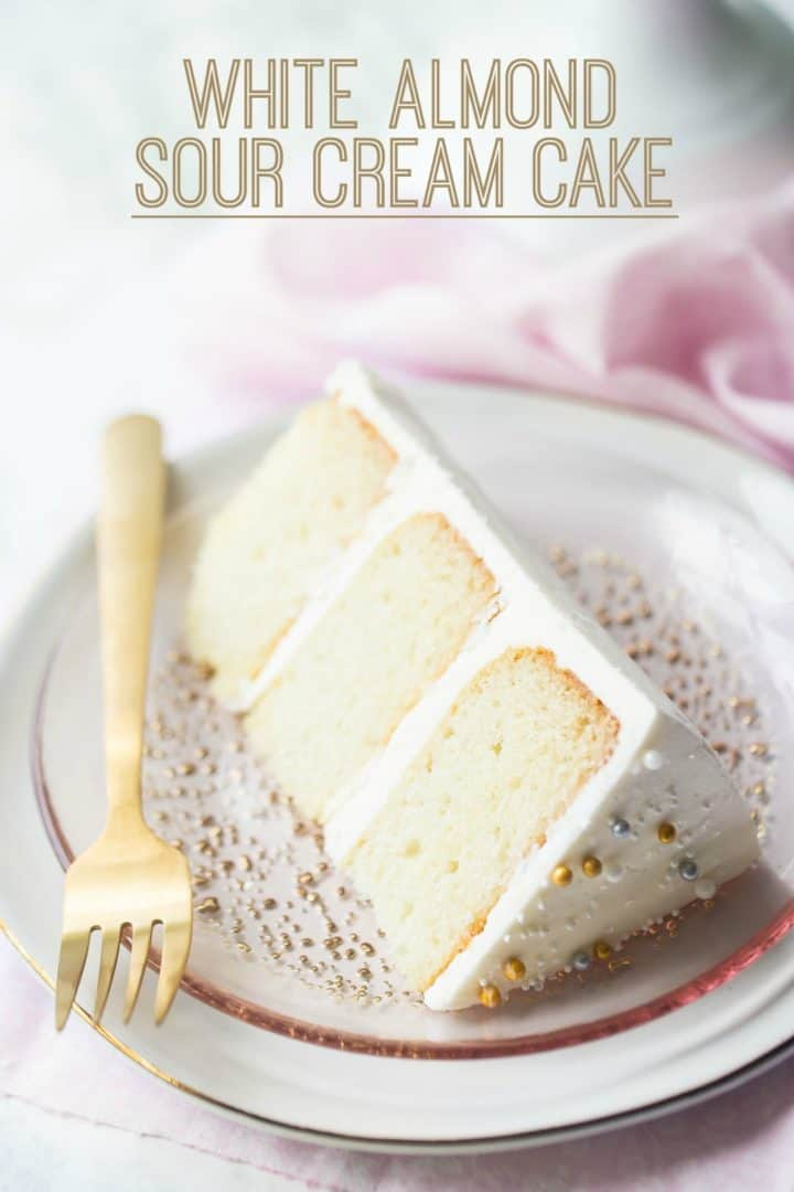 "Slice of white almond sour cream cake laying on its side, on a pink plate with a text overlay reading ""White Almond Sour Cream Cake."""