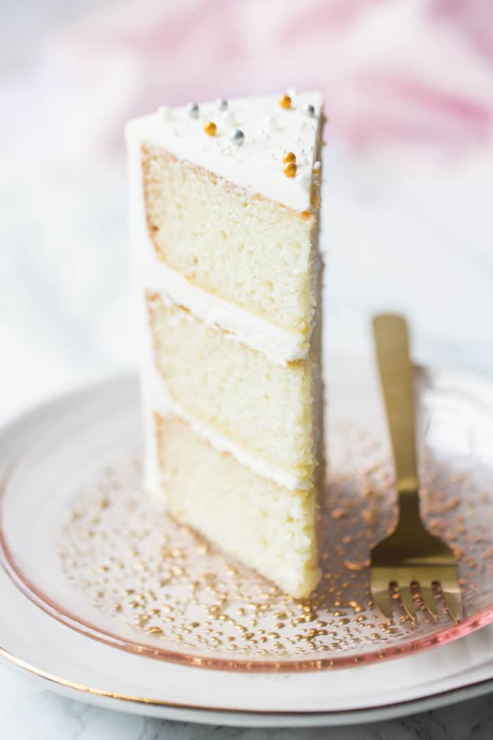 Tall slice of white cake with sour cream, on a pink plate with a gold fork.