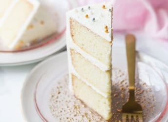 Triple layer slice of white almond sour cream cake on a pink plate.