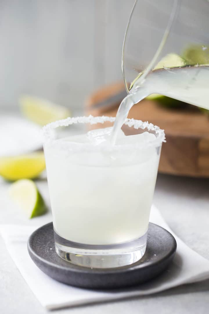 Pouring margarita cocktail over ice into a rocks glass with a salted rim.