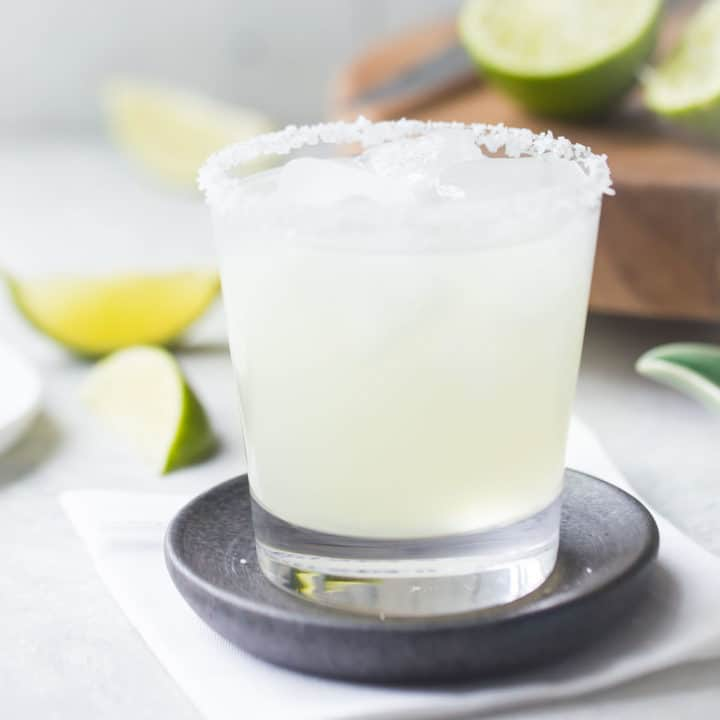 Margarita on the rocks with a salted rim, in a rocks glass with limes in the background.