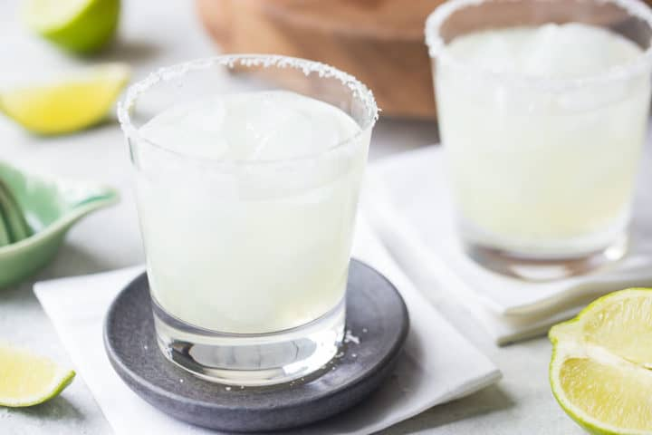 Two margarita cocktails over ice with salted rims and lime wedges in the background.