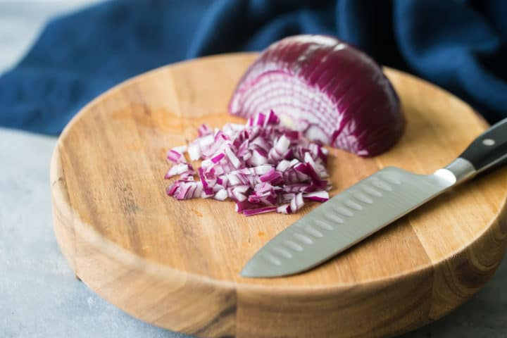 Chopping red onion on a wood cutting board.
