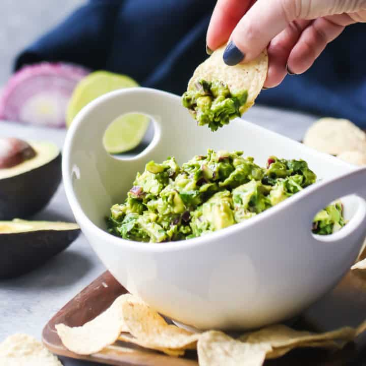 Dipping a corn chip into a bowl of simple guacamole.