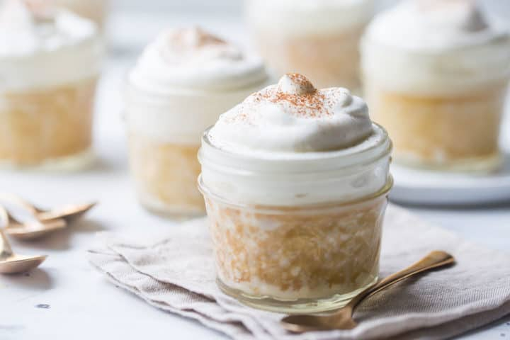 Several individual tres leches cakes baked in glass jars.