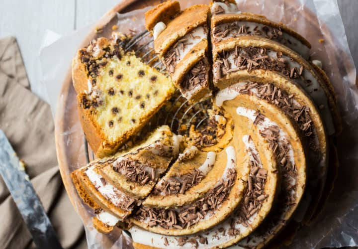 Overhead view of a chocolate chip bundt cake with vanilla glaze and dark chocolate shavings.