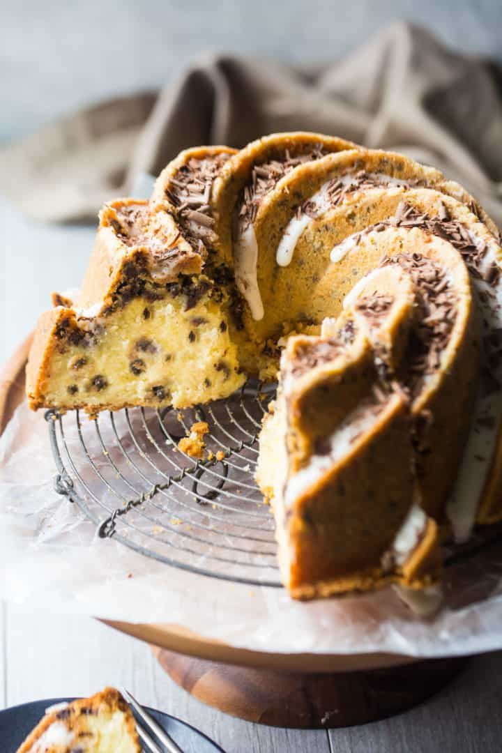 Sliced chocolate chip bundt cake on a cooling rack and pedestal.