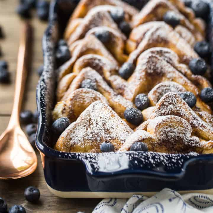 Baked french toast with powdered sugar in a blue casserole dish with a copper serving spoon