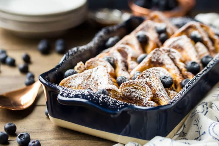 Fresh baked overnight French toast bake in a blue dish with blueberries.