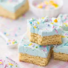 Stack of sugar cookie bars with pale aqua frosting and sprinkles.