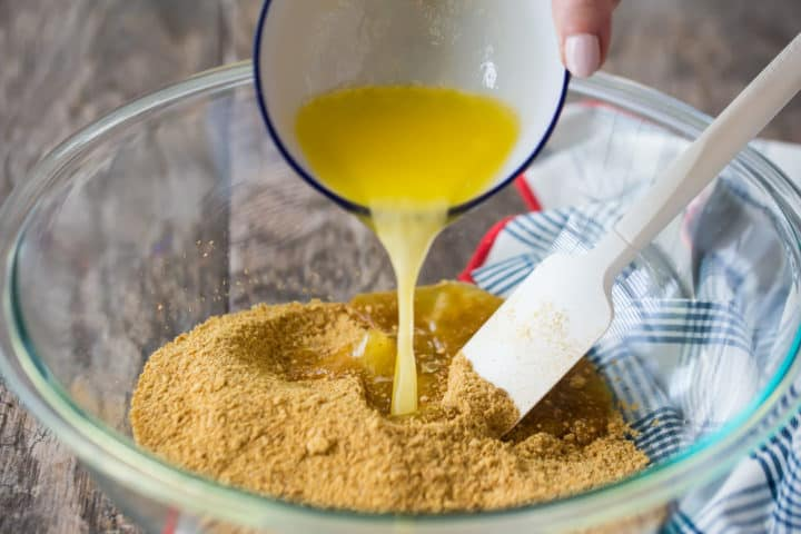 Pouring melted butter into graham cracker mixture.