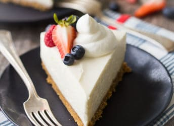 A perfect slice of no-bake cheesecake with whipped cream and berries, on a dark blue plate with a vintage silver fork.