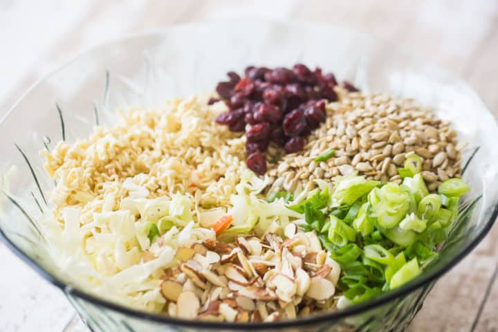 Ramen noodle salad with cabbage, almonds, sunflower seeds, scallions, almonds, and dried cranberries.