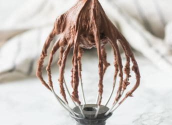 Whisk attachment from a stand mixer with stiffly whipped chocolate ganache.