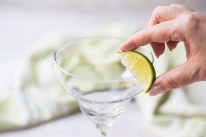Wetting the rim of a margarita glass with lime juice.