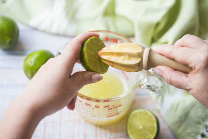 Juicing a lime into a liquid measuring cup with a citrus reamer.