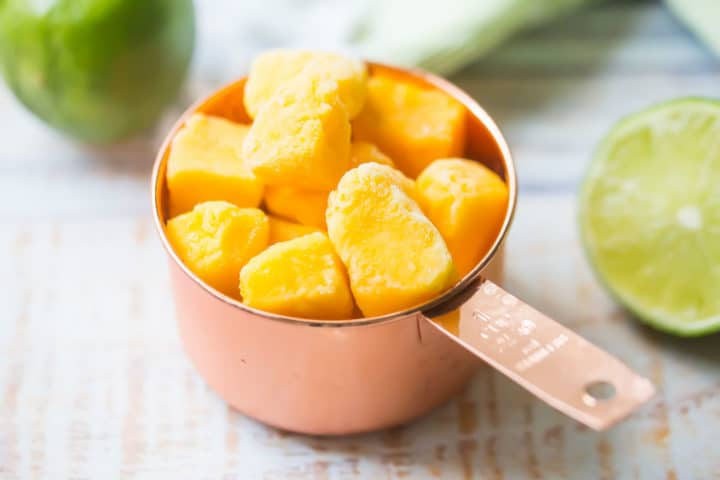 Frozen mango chunks in a copper measuring cup.