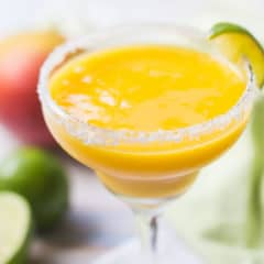 Frozen mango margarita in a salt-rimmed glass with mangoes and limes in the background.