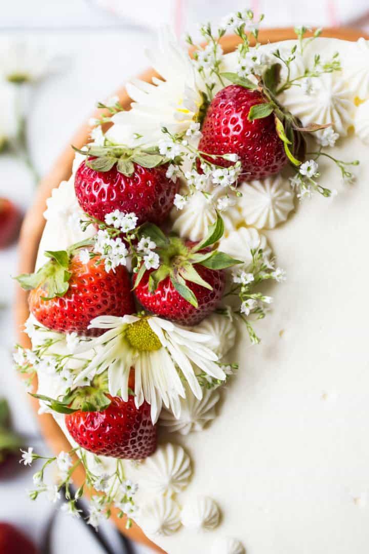 Close-up image of fresh strawberries and flowers on strawberry shortcake cake.
