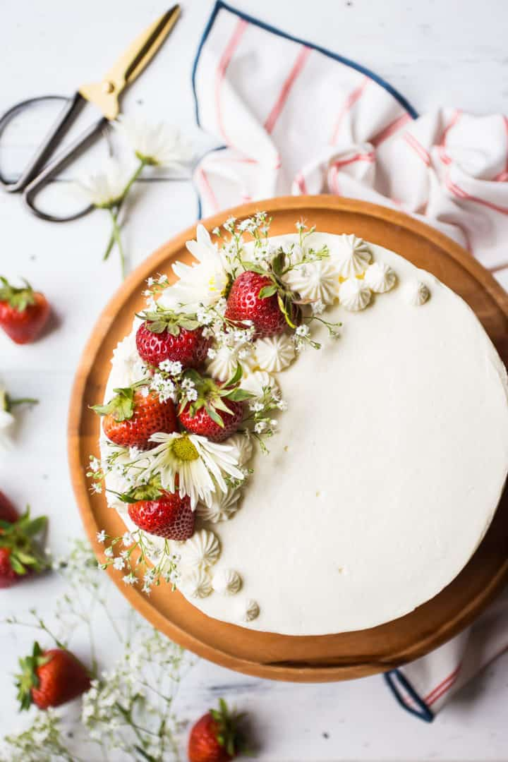Overhead image of a strawberry shortcake cake with strawberries and fresh flowers, on a wooden cake stand.