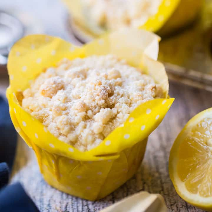 Lemon crumb muffin in a yellow tulip cup with fresh lemon in the background.