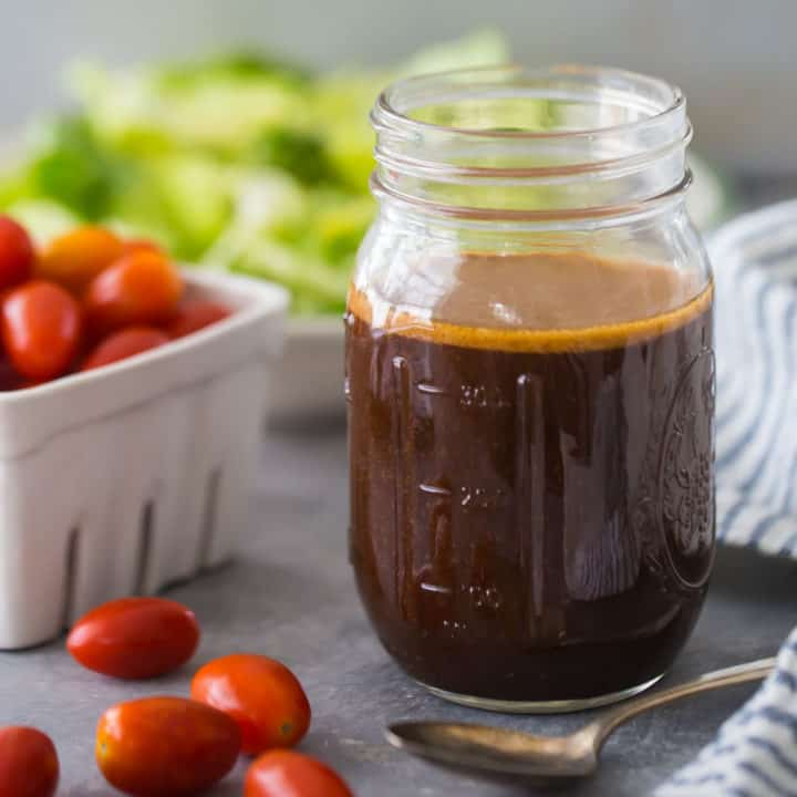 Mason jar of homemade balsamic vinaigrette dressing, with tomatoes and lettuce in the background.