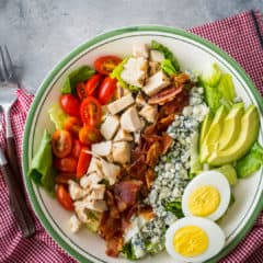 Overhead image of cobb salad in a bowl, with a red checked napkin.