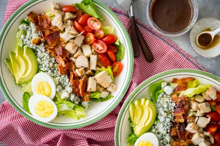 Overhead view of 2 bowls of cobb salad with a jar of homemade vinaigrette and a red checked napkin.