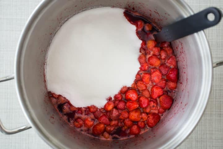Adding sugar to a pot of homemade strawberry jam.