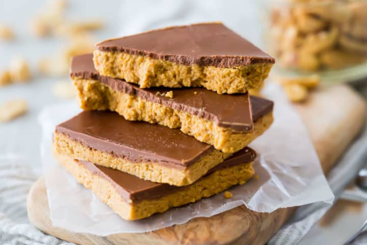 Stacked peanut butter candy bars with a jar of peanuts in the background.