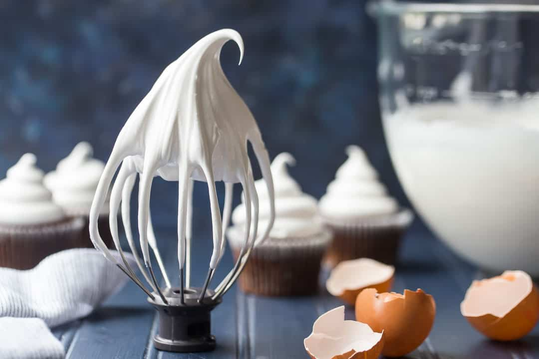 Whisk attachment with marshmallow frosting with egg shells and cupcakes in the background.
