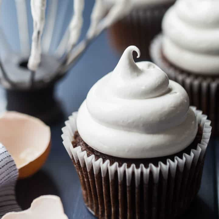 Marshmallow frosting on a cupcake with a whisk in the background.