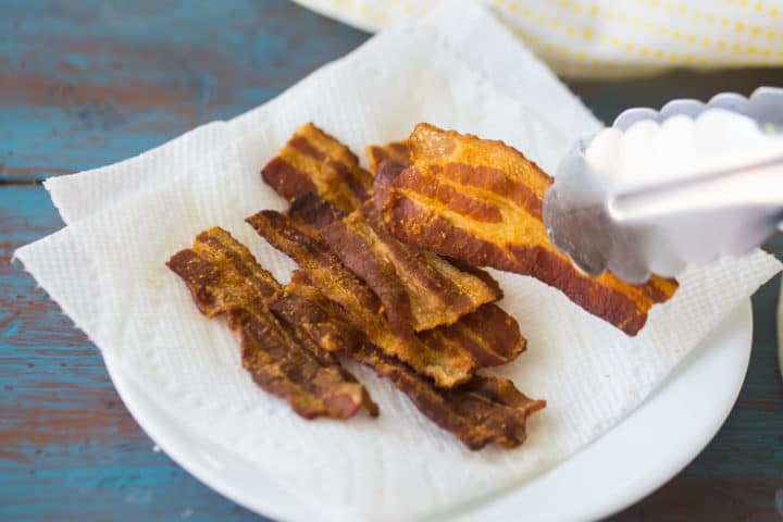 Placing cooked bacon on a plate lined with paper towels.