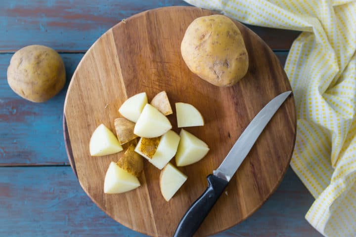 Roughly chopped potatoes on a wooden cutting board.