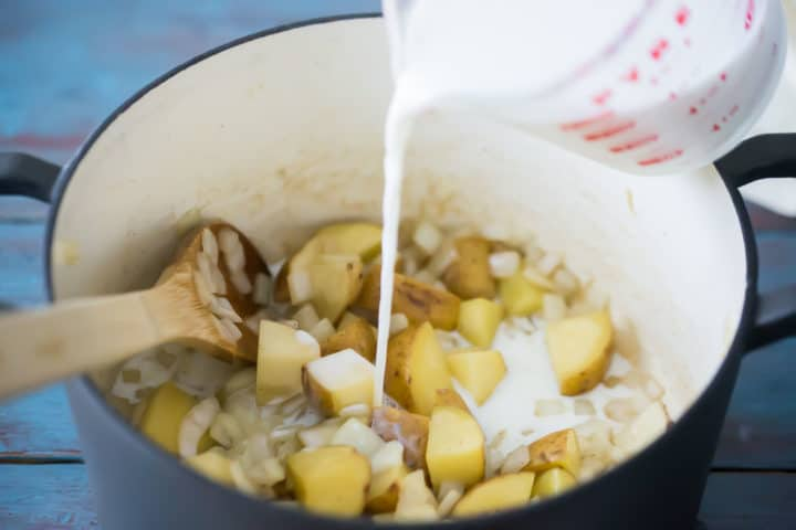 Adding milk to potatoes and onions to make chowder.