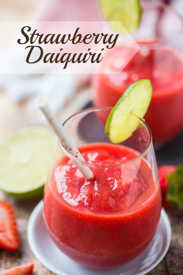 "Two stemless wineglasses with frozen strawberry daiquiris and a text overlay above reading ""Strawberry Daiquiri."""