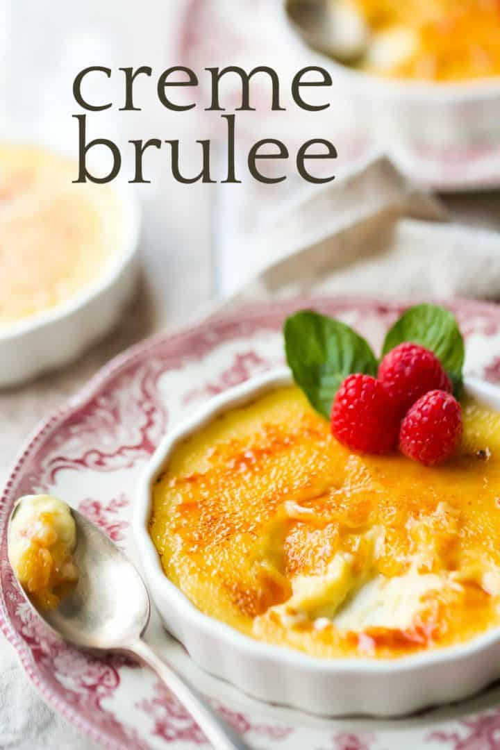 "Shallow dish of creme brulee with a silver spoon and a text overlay reading ""Creme Brulee."""