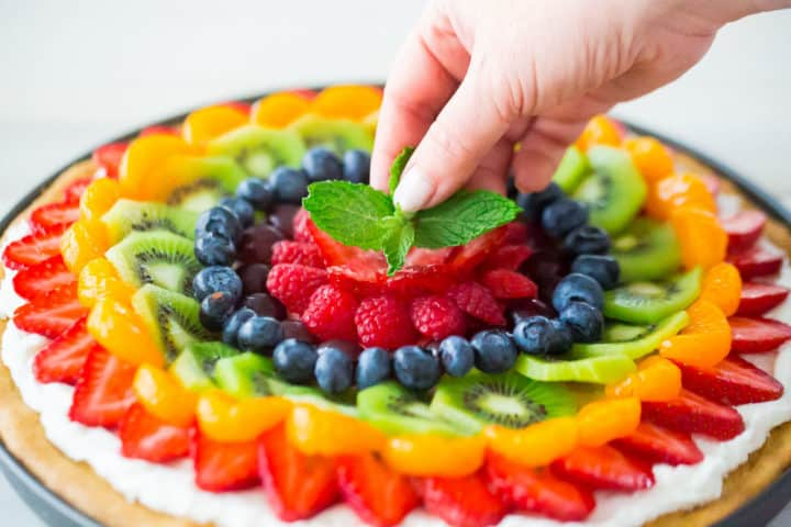 Placing a sprig of fresh mint in the center of a homemade fruit pizza.