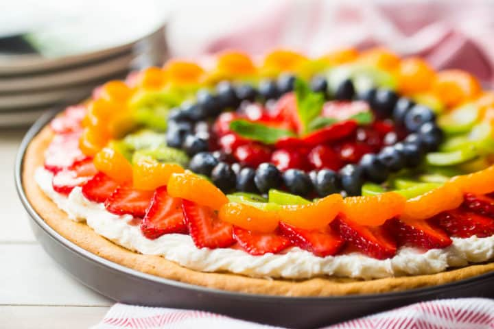 Fruit pizza made from scratch with fresh fruit, cream cheese frosting, and a sugar cookie crust.