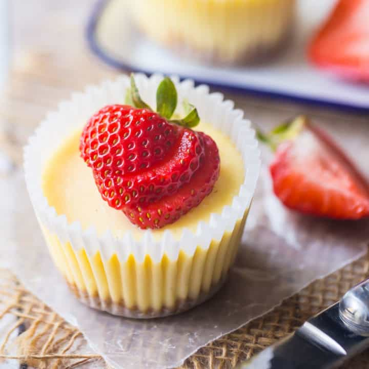 Mini cheesecakes made in a cupcake pan, with graham cracker crust and a fresh strawberry garnish.