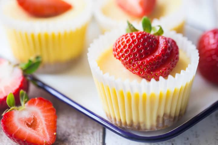 Cheesecake cupcakes on a tray with fresh strawberries.