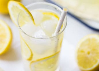 Tall glass of lemonade with ice and slices of fresh lemon.