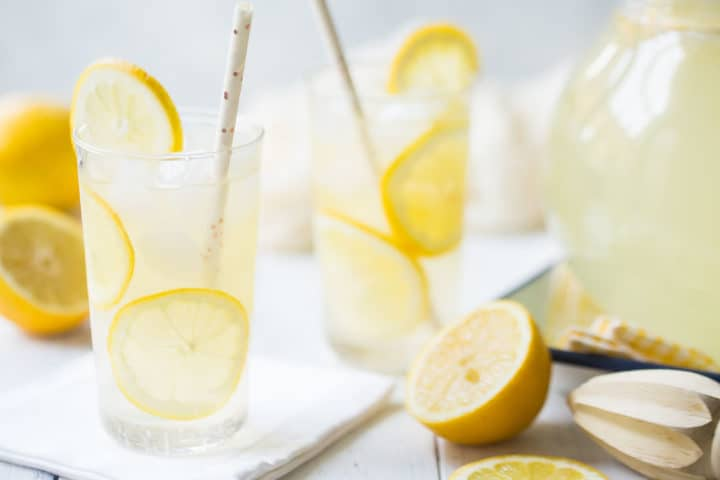 Glasses of homemade lemonade, surrounded by fresh lemons.