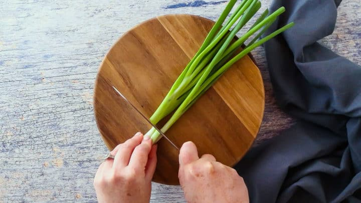Fresh scallions on a wooden cutting board.