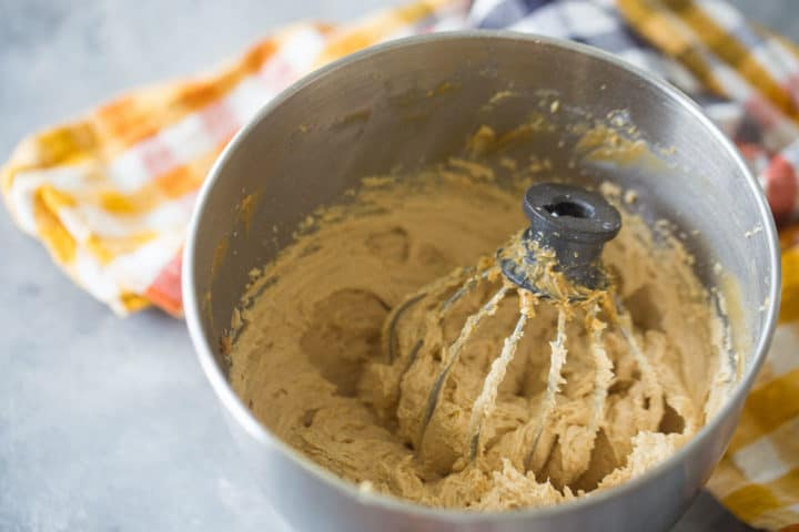 Mixing bowl of peanut butter mousse with a whisk attachment.