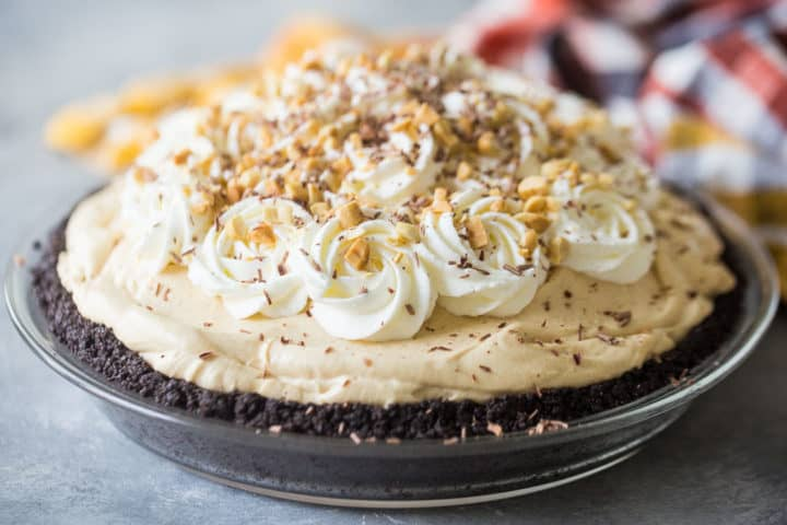 No-bake peanut butter pie with whipped cream, chopped peanuts, and chocolate shavings.