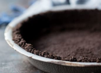 Close-up image of a homemade oreo cookie crust in a vintage pie dish.